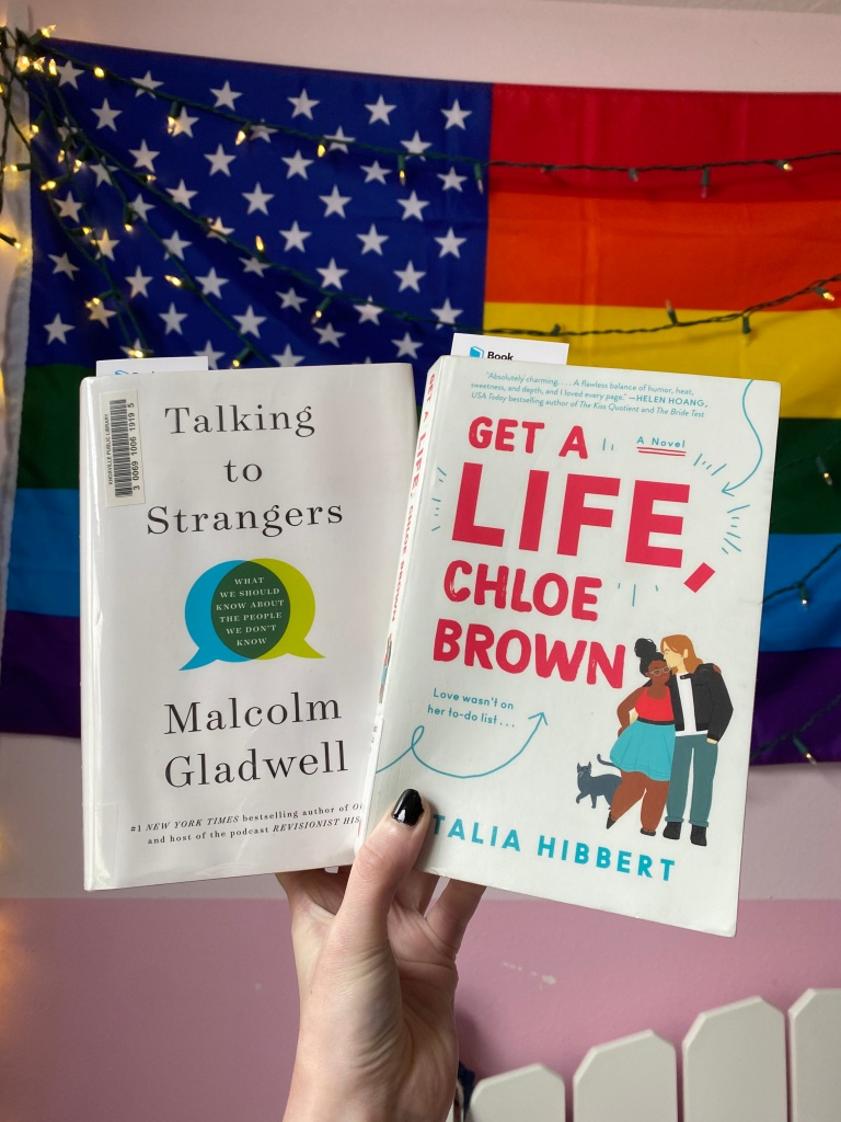 "A hand holding ""Talking to Strangers"" by Malcolm Gladwell and ""Get a Life, Chloe Brown"" by Talia Hibbert."